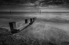 Retreat (SimonTHGolfer) Tags: uk longexposure england sky blackandwhite art beach water monochrome weather clouds contrast landscape mono wooden suffolk waves sigma wideangle filter nd 1020mm groyne felixstowe breakwater landscapephotography ultrawideangle gnd d5100 simontalbothurnphotography