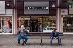 How long does it take to choose Le Creuset? (Silver Machine) Tags: street men shopping magazine bench lumix reading candid streetphotography streetportrait windsor shopwindow berkshire lecreuset lumixg buscoach lumixg20mmf17 lumixg5