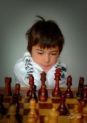 Concentration and Perseverance (rakelgoiri) Tags: boy portrait game retrato boardgame juego concentrate focusing atencion juegodemesa piezasdeajedrez juegodeajedrez chestgame chicochestfigures