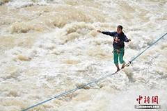 """ท้ามัจจุราช! หนุ่มจีนทำลายสถิติเดินไต่เชือกเส้นเดียว ข้ามหุบเขาเหนือแม่น้ำที่ลึกสุดในโลก (ชมภาพ) (ความรู้ทางฟิสิกส์ เรื่อง สมดุล)      """"จาง เหลียง"""" หนุ่มจีนวัย 31 ปี สร้างความหวาดเสียวด้วยการไต่เชือกขนาด 2.5 เซนติเมตร ข้าม """"ช่องเขาเสือกระโจน""""   http://nuc"""