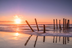 Pointing to the sunrise (Stefan Nikoloff - Photography) Tags: wood sea sky sun seascape beach water clouds sunrise seaside sand nikon waves bright dramatic d750 poles drama 2470mm