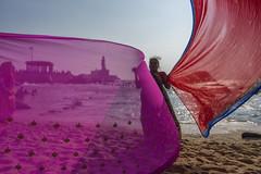 At Kanyakumari (Ravikanth K) Tags: pink red people india beach water statue rock lady sand women memorial wind outdoor clothes southern tip cape cloth activity tamilnadu drying kanyakumari thiruvalluvar sarees vivekananda transperent comorin 500px