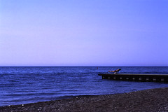 Blue Velvet (azhukau) Tags: blue summer lake film beach water analog outdoor slide sunbath velvia shore serenity fujifilm lakeontario sunbather carlzeiss iso50 contaxrx planart85mmf14