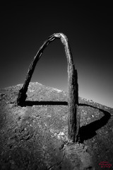 Rusted Handle of a concrete block lining the harbour (eggwah123) Tags: sunset shadow blackandwhite bw abstract texture monochrome closeup contrast zeiss rust fuji harbour outdoor wideangle fujifilm shape concreteblock carlzeiss rustedmetal ultrawideangle xe1 tonality apsc mirrorless xtrans zeisstouit zeiss12mm
