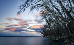 moving the sky (almostsummersky) Tags: longexposure pink blue trees sunset sky lake tree water wisconsin clouds forest us spring movement rocks branch unitedstates sundown wind cloudy bare branches horizon shoreline madison trunk lakemonona