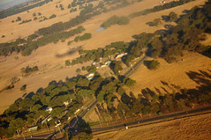 DSC_0632 [ps] - Planes, Lanes & Automobiles (Anyhoo) Tags: road shadow summer brown grass fence landscape countryside flying view roundabout flight dry australia melbourne victoria junction landing pasture hedge vic geography boundary plain arid lowsun dun inflightentertainment viewfrom windbreak viewfromtheplane anyhoo planeshadow somertonroad oaklandsroad photobyanyhoo
