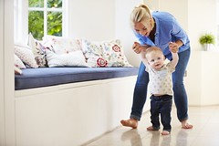 Mother Helping Young Son As He Learns To Walk (TeeWilson) Tags: family boy people woman cute male smiling horizontal female laughing walking children happy person holding hands women toddler child walk mother son indoors mum parent together learning copyspace twopeople 20s havingfun caucasian twenties 9monthold
