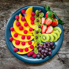 Colorful fruits and berries on big blue plate. On rustic wooden background. Top view. (locrifa) Tags: red summer food color green fruits beautiful closeup breakfast table dessert salad spring healthy strawberry colorful berries view natural sweet top background strawberries tasty plate bowl row fresh delicious mango grapes tropical raspberry organic colourful variety diet kiwi vitamins