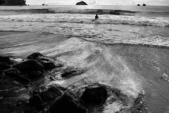 Lone swimmer (halifaxlight) Tags: ocean bw man beach islands costarica rocks surf alone pacificocean solo swimmer manuelantonio