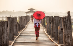 Burmese woman (Bugphai ;-)) Tags: wood travel bridge red people woman girl beautiful umbrella sunrise asian gold wooden asia warm burma traditional bein u myanmar burmese mandalay bagan unidentified