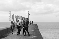 Curious dance, Porthleven Quay bw (chrisotruro) Tags: sea people pier dance spring cornwall flags shore april porthleven
