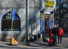 Walking around, looking around (R A Pyke (SweRon)) Tags: life street boy woman baby man closed day carriage sweden scene every fujifilm pram drycleaner rebro kemtvtt xpro1 sweron ekersgatan fujinon35mmf14 201602281745