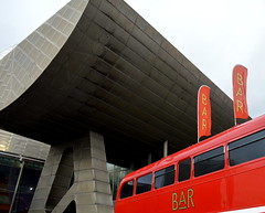 Red bus with banners under the Lowry at Manchester (Tony Worrall Foto) Tags: county new city uk travel england color building bus lines metal architecture modern manchester design stream colours tour open place northwest unitedkingdom centre country north angles salfordquays visit location area blocks banners northern trafford update salford lowry quirky attraction manc redbus gmr welovethenorth