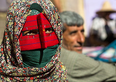 a bandari woman wearing the traditional mask called the burqa on a market, Hormozgan, Bandar Abbas, Iran (Eric Lafforgue) Tags: red people man horizontal outdoors persian clothing couple asia veil mask iran market muslim islam religion hijab persia tribal hidden covered iranian bazaar 2people twopeople adultsonly islamic burqa middleeastern persiangulf sunni bandarabbas burka middleagedman chador youngadultwoman balouch hormozgan burqua   embroidering  iro straitofhormuz  colourpicture  borqe boregheh iran034i1947