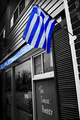 *The Old Greek Flag* (Poocher7) Tags: blackandwhite ontario canada monochrome shop reflections greek bakery shutters markham greekflag   greekbakery