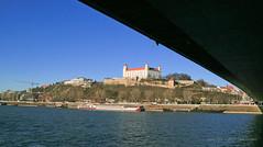 Dec 30: Bratislava - Castle under Bridge (johan.pipet) Tags: city winter castle history canon river landscape boat town december ship hill sunny most stare slovensko slovakia palo bratislava danube hrad donau bartos mesto rieka snp bridhe dunaj kopec barto