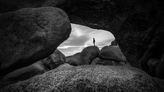 Arch rock - Joshua tree national park, USA - Black and white street photography (Giuseppe Milo (www.pixael.com)) Tags: california street travel sky blackandwhite bw usa white black tree girl monochrome rock clouds contrast geotagged photography us photo nationalpark rocks alone arch fuji unitedstates joshua candid joshuatree streetphotography faceless fujifilm onsale joshuatreenationalpark fujix xt10 fujixt10