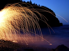 Fire & Water (Karen_Chappell) Tags: ocean longexposure blue orange hot cold beach water yellow night newfoundland fire evening elements sparks nfld middlecove middlecovebeach spinningsteelwool