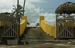Stairs to Palms (BradPerkins) Tags: wood dominicanrepublic abandoned tiki palmtrees stairs gate urbanlandscape empty yellow bar