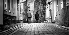 Saturday Stroll (Mister G.C.) Tags: life street old city people urban blackandwhite bw woman man monochrome germany lens deutschland photography prime nikon couple europe shot image candid streetphotography 85mm photograph elderly frombehind nikkor dslr unposed schwarzweiss niedersachsen lowersaxony 18g lowpov lowpointofview strassenfotografie d5300 strassenphotographie mistergc