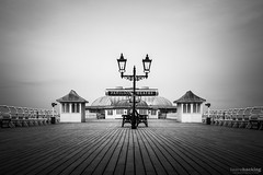 Cromer Pier (laura.hacking) Tags: old uk longexposure travel england blackandwhite holiday tourism lamp monochrome architecture vintage lights mono evening coast pier wooden quiet unitedkingdom britain outdoor norfolk wide victorian overcast landmark location symmetry resort lampost symmetrical british seafront bnw eastanglia oldfashioned cromer fineartphotography blackandwhitephotography leadinglines project52 appicoftheweek