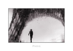 Paris n49 Man Under The Tower (Nico Geerlings) Tags: paris france monument rain silhouette reflections 50mm eiffeltower toureiffel summilux champsdemars parijs gustaveeiffel nicogeerlings leicammonochrom ngimages nicogeerlingsphotography