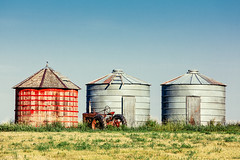Three Bins (www.toddklassy.com) Tags: old blue sky west color field grass rural montana mt exterior unitedstates farm horizon country farming rustic harvest nobody nopeople farmland storage clear ridge silos copyspace shelter bins tranquil containers oldfashioned grassy grainbins wester lewistown farmbuildings quain ferguscounty