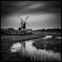 The Mill and the Wind (Luke Hanna) Tags: sky bw white black reflection mill water windmill clouds river reeds stream long exposure wind le marsh marshes cley