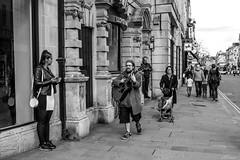 Unwelcome Serenade (Silver Machine) Tags: street man girl walking lumix waiting guitar outdoor candid streetphotography oxford oxfordshire guitarist lumixg lumixg20mmf17 lumixg5