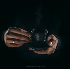 Man hands with cup of coffe close up image (CreativePhotoTeam.com) Tags: life old morning people food brown black hot art cup coffee businessman breakfast night vintage dark person cafe still holding warm break hand flavor darkness tea drink coffeecup finger background beverage style fresh steam ring business enjoy espresso taste concept caffeine cappuccino aromatic isolated mafia roasted aroma smelling fingerring justprepared
