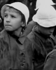 Why do all these soldiers lining the street have guns (theirhistory) Tags: girls boys hat kids children shoes war europe wwii ww2 soldiers raincoats germans