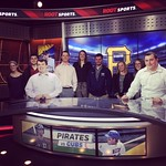 Students pose for a photo behind a news desk at ROOT Sports