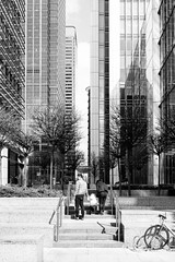 Through skyscrapers (lorenzoviolone) Tags: family trees england people blackandwhite bw london monochrome bike skyscraper parents blackwhite kid unitedkingdom streetphotography finepix fujifilm streetphoto canarywharf fav10 agfascala200 mirrorless vsco streetphotobw vscofilm fujix100s x100s fujifilmx100s travel:uk=londonapr16