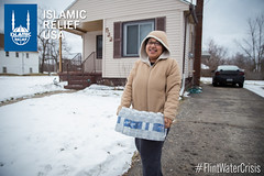 Shanandra receives a case of water bottles from Islamic Relief USA.