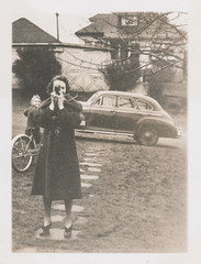 Woman taking a photo of the camera person in the front yard (simpleinsomnia) Tags: camera old woman white black monochrome car bicycle vintage found blackwhite photographer antique snapshot lawn front photograph vernacular frontlawn foundphotograph