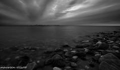 Rocks and Clouds (maureen.elliott) Tags: sunset blackandwhite lighthouse water clouds landscape outdoors island evening skies shoreline lakehuron