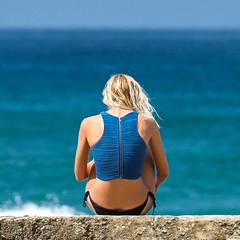 Girl on the beach (Stelex) Tags: ocean blue portrait ass beach girl wall female swim hair naked nude concrete back sitting skin horizon arse windy australia bum blonde queensland faceless beachbabe swimsuit swimwear beachbum goldcoast beachwear