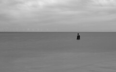 Stranded (Andrew Gibson.) Tags: sea sky blackandwhite bw men beach water statue liverpool coast sand waves alone tide statues castiron crosby antonygormley sefton anotherplace crosbybeach siranthonygormley sonya7ii