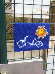 A Sunny Ride (mdavidford) Tags: blue sun smile bicycle knitting gate mesh entrance colourful bikeshed oxfam guerillaknitting knitbomb yarnbomb