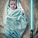 My 4-weeks-old Jedi with a lightsaber.
