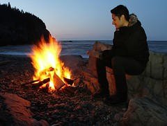 Warm Fire (Karen_Chappell) Tags: blue people orange beach night newfoundland fire person evening flame nfld middlecove middlecovebeach avalonpeninsula