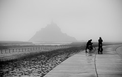 Le Mont Saint-Michel (Missy Jussy) Tags: trip travel people bw mist france tourism monochrome bicycle silhouette fog canon fence buildings landscape mono blackwhite village transport tourists estuary monastery boardwalk historical walkways normandy biketrip lemountsaintmichel cannon600d