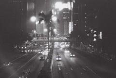 Evening, Hong Kong (Jon Siegel) Tags: road city light urban bw film misty night hongkong 50mm lights evening blackwhite nikon highway palmtrees 12 nikkor ilford nikonfe2 50mmf12 nikkor50mmf12ais
