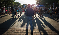The Man in the Hat (Anne Worner) Tags: people sun walking outside outdoors evening lowlight texas wideangle georgetown ricohgr contrejour strongcontrast rimlight streetstreetphotography silverefex anneworner 2016poppyfestival