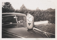 Jack-o-lantern sitting on the hood of a car (simpleinsomnia) Tags: old white black halloween monochrome car vintage pumpkin found blackwhite jackolantern antique snapshot photograph vehicle hood vernacular foundphotograph