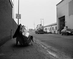Crushed Wheelie Bin - Middlesbrough. (Richard James Palmer) Tags: street new uk england urban blackandwhite white black art 120 mamiya film monochrome newcastle landscape photography landscapes trapped shoot gloomy iso400 fineart north documentary overcast rangefinder gritty ishootfilm tyne east iso ilfordhp5 400 walkabout epson hp5 medium format analogue melancholy northern northeast ilford f4 isolated upon newcastleupontyne 1125 80mm tyneandwear 2016 v700 mamiya7ii microphen filmisnotdead 7ii ilfordmicrophen epsonperfectionv700
