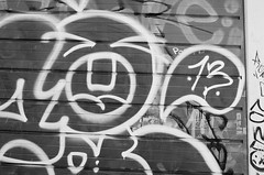13 (Georgie_grrl) Tags: door friends blackandwhite streetart toronto ontario face graffiti expression garage photographers social pentaxk1000 13 tagging outing ilford400asa rikenon12828mm torontophotowalks seatonvillagesaturdayscramble topwsvss