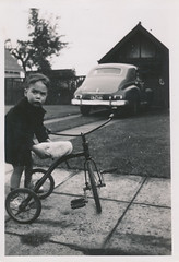 Concerned-looking little boy getting on a tricycle (simpleinsomnia) Tags: old boy white black monochrome vintage found outside blackwhite little antique tricycle snapshot photograph vernacular littleboy concerned foundphotograph