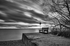 Watching time pass (jarnasen) Tags: longexposure sky blackandwhite bw copyright lake tree beach nature water monochrome clouds contrast bench landscape mono pier movement nikon mood conversion noiretblanc sweden outdoor branches tripod smooth surface le sverige scandinavia linkping landskap svartvit movingclouds ndfilter roxen d810 leefilters nd10 ekngen nordiclandscape bigstopper 1635mmf4 jarnasen