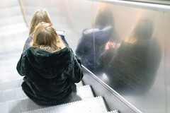 2 x 2 (Gerd Trynka-Ottosohn) Tags: girls reflection germany escalator napoli spiegelung mädchen rolltreppe movingstaircase sitzend gerdtrynka xf56mmf12 ottosohnfoto fujixt10